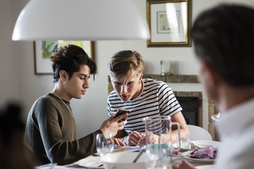 Friend showing phone to teenage boy while sitting at dinner party