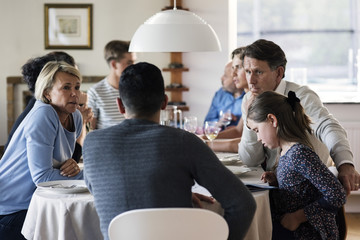 Multi-ethnic friends and family talking at dining table in dinner party