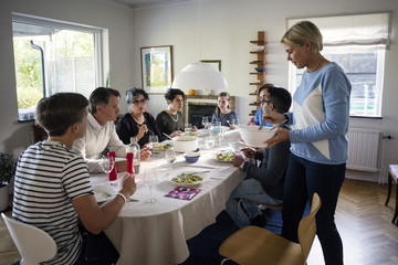 Woman serving food to family and friends at dining table in dinner party