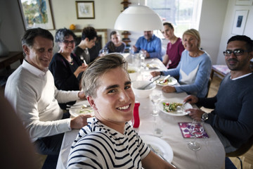 High angle view of smiling teenage boy taking selfie with family and friends at dining table