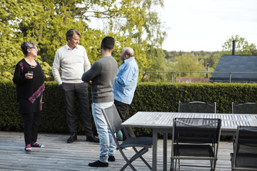 Multi-ethnic friends talking while standing by table in yard
