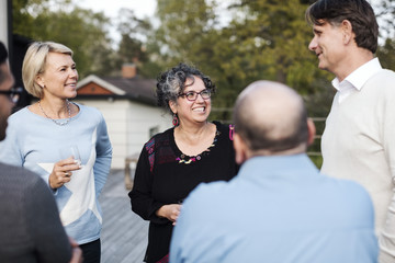 Happy multi-ethnic friends talking while having drink in yard