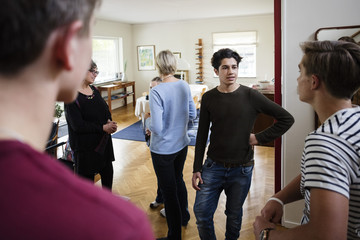 Multi-ethnic friends talking with family while standing in living room