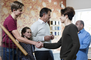 Multi-ethnic friends shaking hands while family greeting in living room