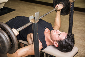 Handsome muscular young man using barbell in gym on bench