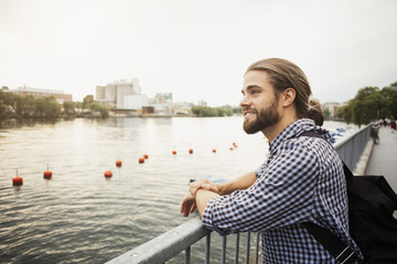 Thoughtful smiling man standing at railing by river in city against clear sky