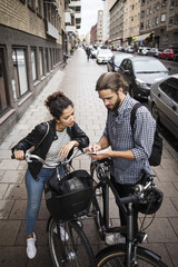 Friends with bicycles using mobile phone while standing on sidewalk