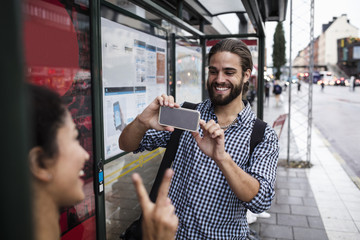 Smiling man photographing female friend through smart phone at bus stop in city