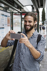 Man taking photograph with smartphone at bus stop