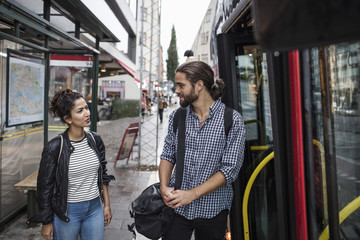 Friends talking while standing by bus in city