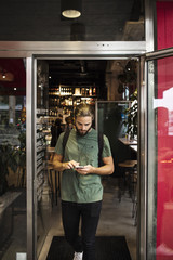 Full length of man using mobile phone while walking at restaurant doorway