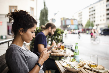 Side view of woman text messaging while having food at sidewalk cafe in city