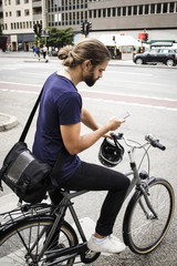 Man with bicycle using mobile phone while standing on city street