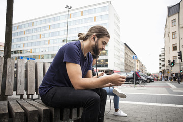 Man listening music through smart phone while sitting beside woman on wooden bench in city