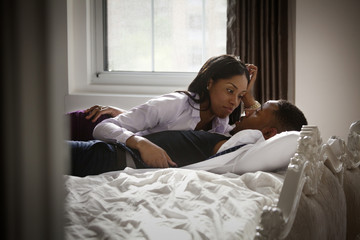 Well-dressed couple lying on bed