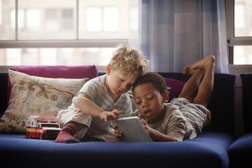 Boys (2-3, 4-5) using tablet on sofa
