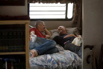 Gay couple lying in bed in motor home