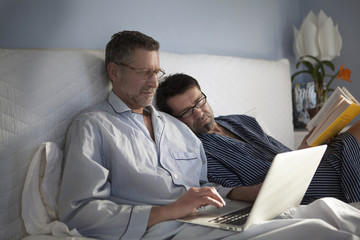 Mature gay couple looking at laptop while sitting on the bed