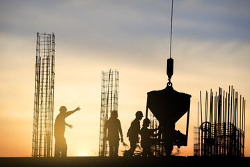 Silhouettes of workers at a construction site