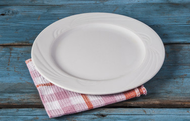Empty plate with napkin on blue wooden table