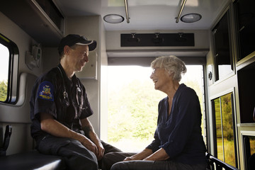 Senior woman talking to paramedic in ambulance
