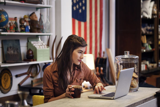 Young woman using laptop while drinking coffee