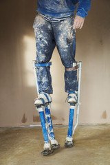 Plasterer wearing stilts