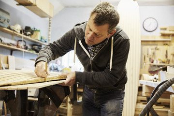Man working on the edge of a wooden shaped board in a woodwork shop.