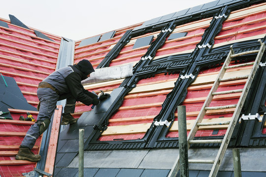 A roofer replacing the tiles on a house roof.
