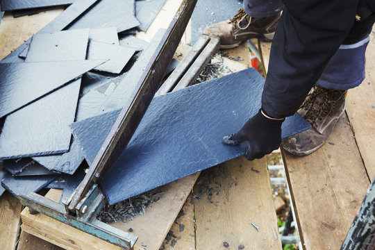 A man cutting a tile with a large guillotine blade.