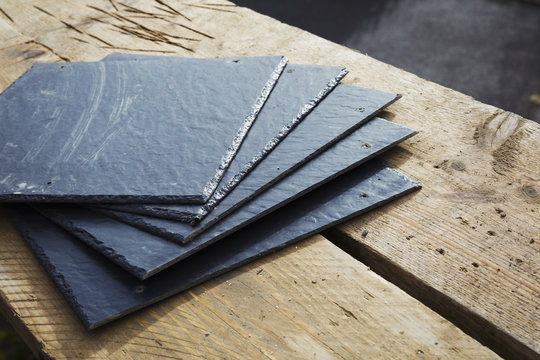 A pile of slate tiles on a wooden surface.