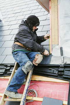 A man at the top of a ladder on a house roof, fixing tiles on a dormer roof.