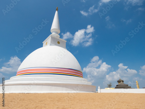 White Stupa Dagabo On Sand Wrapped With Buddhist Flag And Blue Sky Clouds Temple