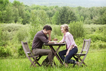 Couple laughing over birthday cake while sitting outdoors