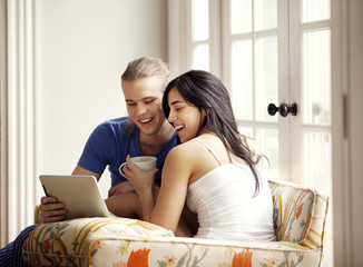 Couple looking at digital tablet on couch