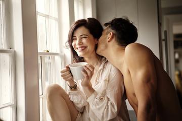 Man kissing teasing woman over coffee