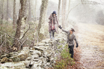 Man guiding woman on stone wall