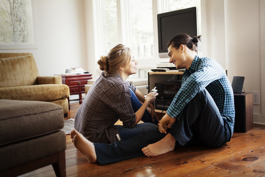 Young couple listening to music on living room floor