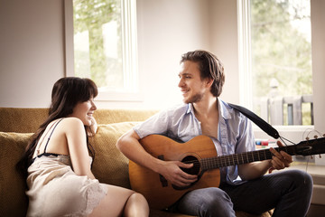 Young man playing guitar for his girlfriend on couch