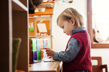 Boy (2-3) standing by desk and playing