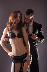 Elegant couple: a man in a suit and a young woman in lingerie.