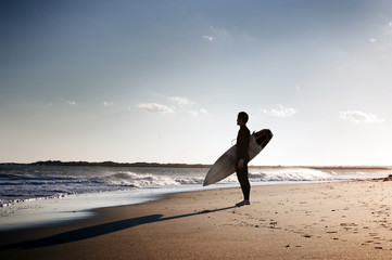 Surfer sitting on sandy beach and holding surfboard