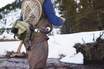 Mid section of man fly-fishing on mountain river in winter