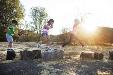View of children ( 4-5, 6-7, 8-9 ) playing on tree stump
