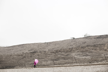Little girl (6-7) walking with umbrella on cloudy day