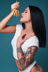 Beautiful charming tattoo girl with french fries