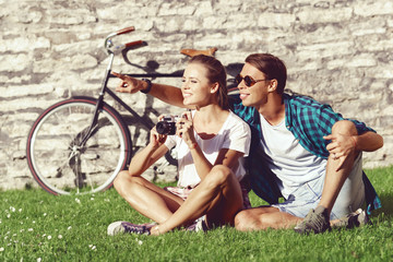 Young couple of hipsters taking pictures in a park. Love, relationship, romance concept.