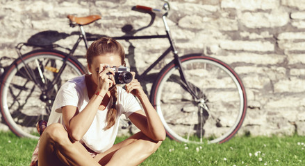 Beautiful hipster girl taking pictures in a park. Holiday, vacation, traveling concept.