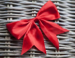 nœud rouge cadeau sur fond de rotin