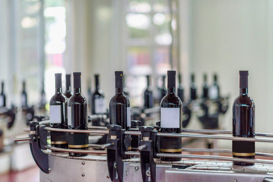 Red wine bottling and sealing conveyor line at winery factory